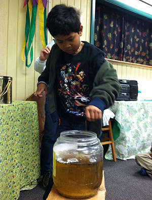 Boy measuring water into jar.