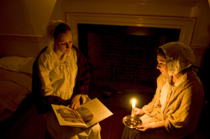 Girls reading by candlelight.
