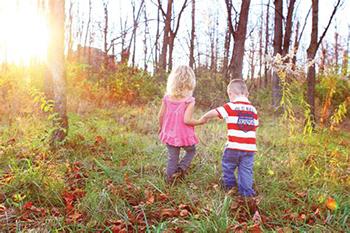 Girl and boy walking in a field.
