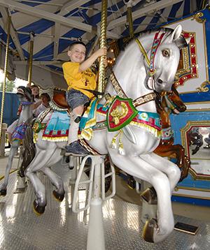 Boy riding carousel horse.