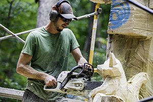 Man carving wood with chainsaw.