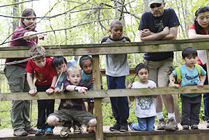 Adults and children on wooden bridge in the woods.