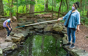 Child and woman holding a net over a stream.