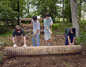 Four young men work on a drainage pipe.