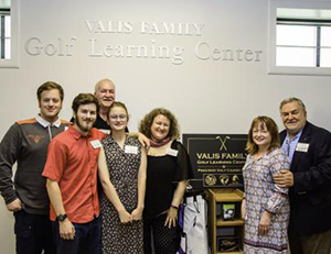 Valis family stand in front of Valis Family Golf Learning Center sign.